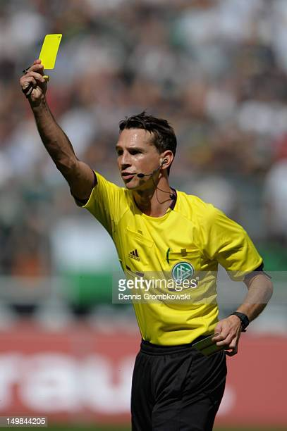 Referee Christian Bandurski shows a yellow card during the friendly match between Borussia Moenchengladbach and FC Sevilla at BorussiaPark on August...