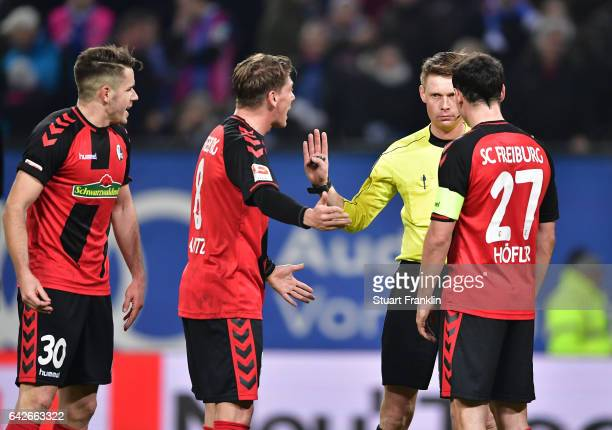 Referee Christian Dingert gestures to Mike Frantz and Nicolas Hfler of Freiburg during the Bundesliga match between Hamburger SV and SC Freiburg at...