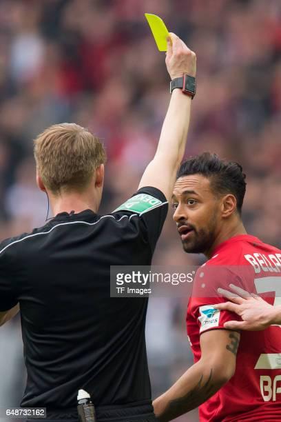 Referee Christian Dingert gives Karim Bellarabi of Bayer Leverkusen the yellow card during the Bundesliga match between Borussia Dortmund and Bayer...