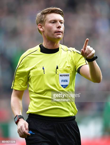 Referee Christian Dingert points during the Bundesliga match between Werder Bremen and RB Leipzig at Weserstadion on March 18 2017 in Bremen Germany