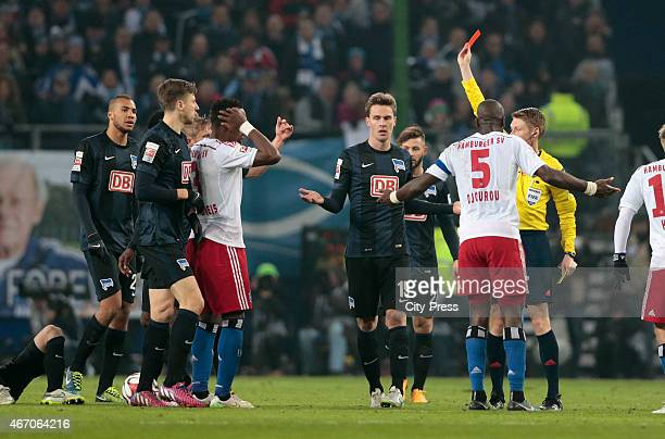 Referee Christian Dingert shows Cleber Janderson Pereira Reis of Hamburger SV the yellow card during the match between Hamburger SV and Hertha BSC on...