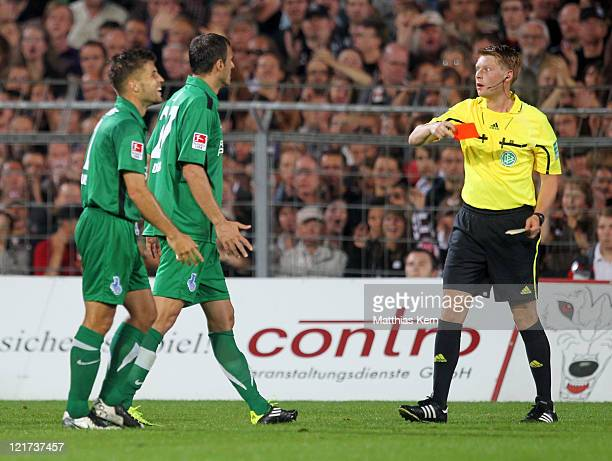 Referee Christian Dingert shows the red card to Vasilios Pliatsikas of Duisburg during the Second Bundesliga match between FC St Pauli and MSV...