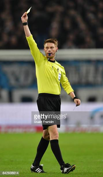 Referee Christian Dingert shows the yellow card during the Bundesliga match between Hamburger SV and SC Freiburg at Volksparkstadion on February 18...