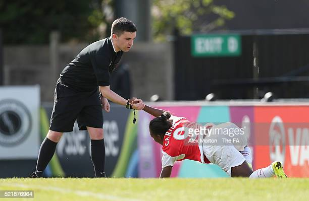 Referee Christopher O'Donnell helps up Dan Carter of Arsenal after scoring their seventh goal during the SSE Women's FA Cup Semifinal match between...