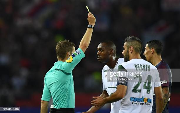 Referee Clement Turpin shows a yellow card during the French L1 football match between Paris SaintGermain and SaintEtienne on August 25 at the Parc...