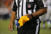 A referee collects his penalty flag as the Seattle Seahawks face the Denver Broncos during preseason action at Sports Authority Field at Mile High on...