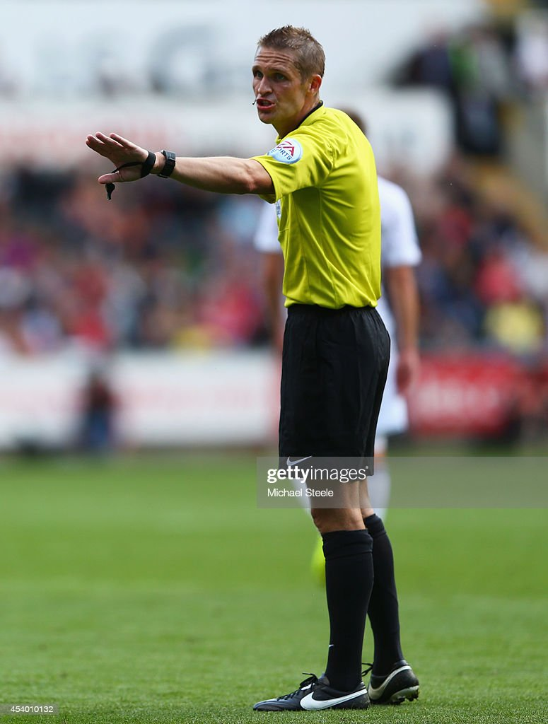 Referee Craig Pawson signals during the Barclays Premier League match between Swansea City and Burnley at Liberty Stadium on August 23, 2014 in Swansea, Wales.