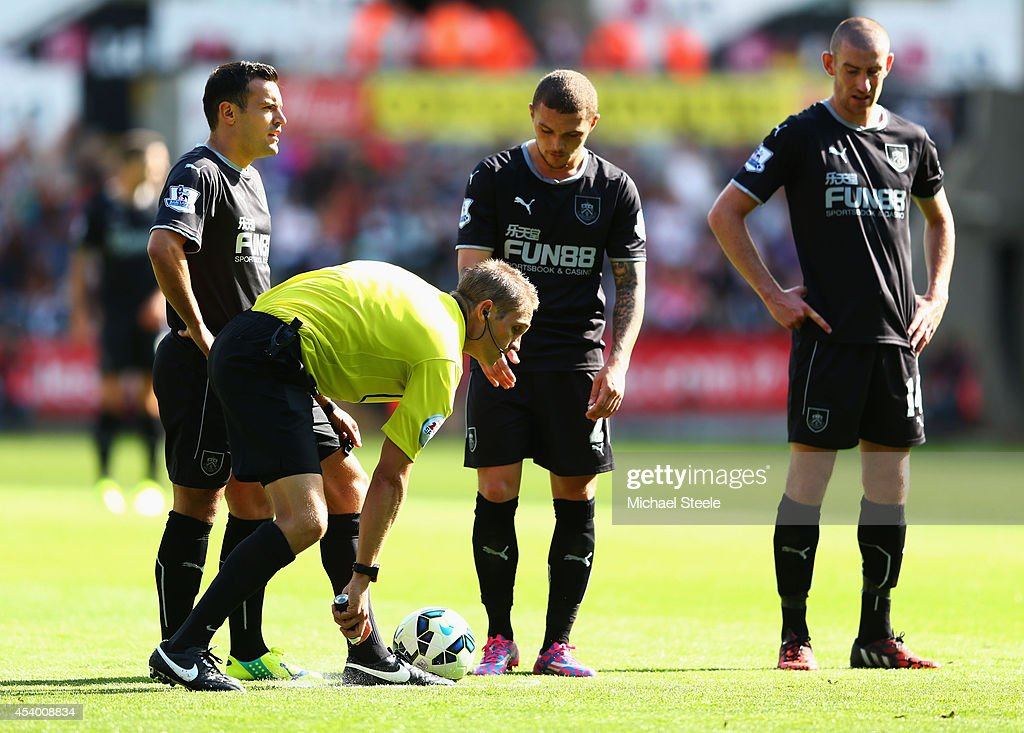 Referee Craig Pawson uses vanishing spray during the Barclays Premier League match between Swansea City and Burnley at Liberty Stadium on August 23, 2014 in Swansea, Wales.