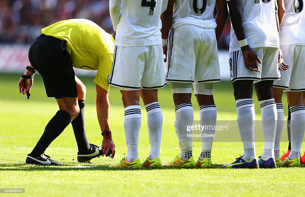 Referee Craig Pawson uses vanishing spray to mark out a defensive wall during the Barclays Premier League match between Swansea City and Burnley at Liberty Stadium on August 23, 2014 in Swansea, Wales.