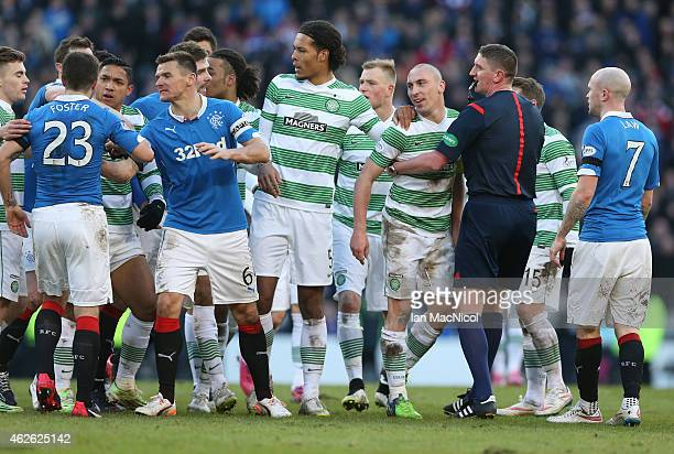 Referee Craig Thomson holds back Celtic's captain Scott Brown during the Scottish League Cup SemiFinal football match between Celtic and Rangers at...