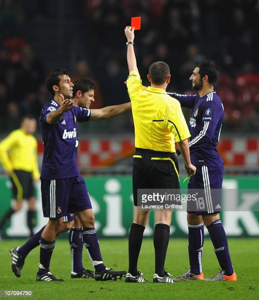 Referee Craig Thomson of Scotland sends off Xabi Alonso of Real Madrid for time wasting during the UEFA Champions League Group G match between AFC...