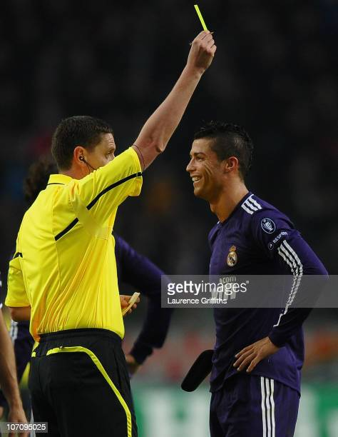 Referee Craig Thomson of Scotland shows the yellow card to Cristiano Ronaldo of Real Madrid for time wasting during the UEFA Champions League Group G...