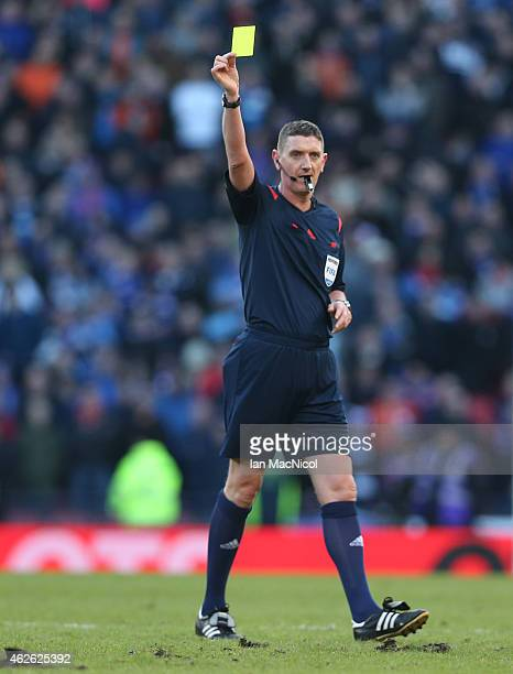 Referee Craig Thomson shows a yellow card during the Scottish League Cup SemiFinal football match between Celtic and Rangers at Hampden Park on...