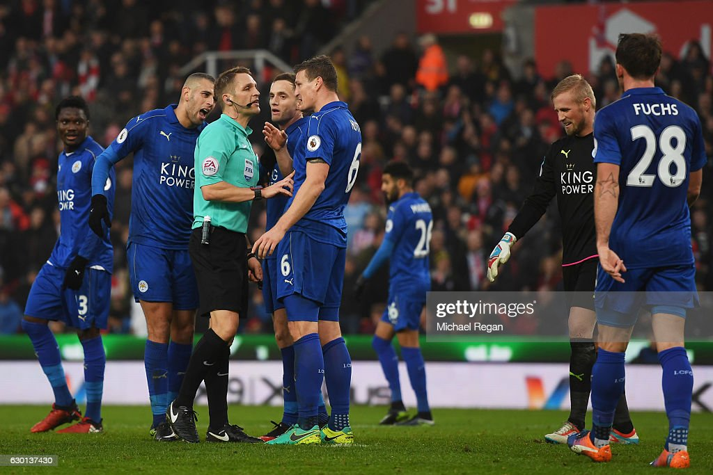 Referee Criag Pawson argues with Robert Huth of Leicester City (C) during the Premier League match between Stoke City and Leicester City at Bet365 Stadium on December 17, 2016 in Stoke on Trent, England.