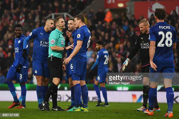 Referee Criag Pawson argues with Robert Huth of Leicester City during the Premier League match between Stoke City and Leicester City at Bet365...