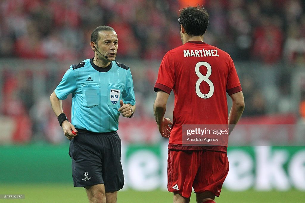 Referee Cuneyt Cakir (L) conducts the UEFA Champions League semifinal second leg soccer match between FC Bayern Munich and Atletico Madrid at the Allianz Arena in Munich, Germany on May 3, 2016.