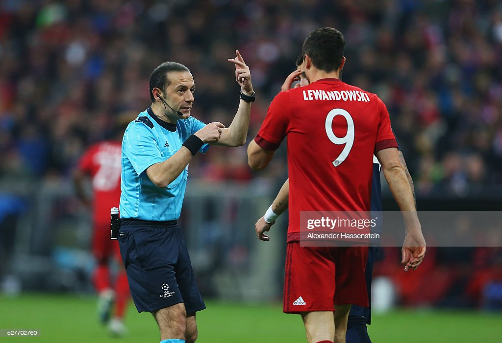 Referee Cuneyt Cakir in discussion with <a gi-track='captionPersonalityLinkClicked' href=/galleries/search?phrase=Robert+Lewandowski&family=editorial&specificpeople=5532633 ng-click='$event.stopPropagation()'>Robert Lewandowski</a> of Bayern Munich during UEFA Champions League semi final second leg match between FC Bayern Muenchen and Club Atletico de Madrid at Allianz Arena on May 3, 2016 in Munich, Germany.