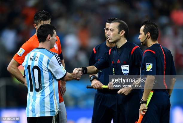 Referee Cuneyt Cakir shakes hands with Lionel Messi of Argentina at the end of the normal time during the 2014 FIFA World Cup Brazil Semi Final match...