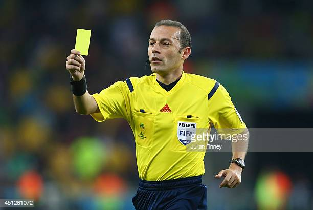 Referee Cuneyt Cakir shows a yellow card during the 2014 FIFA World Cup Brazil Group H match between Algeria and Russia at Arena da Baixada on June...