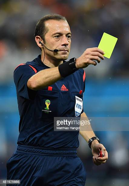 Referee Cuneyt Cakir shows a yellow card to Bruno Martins Indi of the Netherlands during the 2014 FIFA World Cup Brazil Semi Final match between the...
