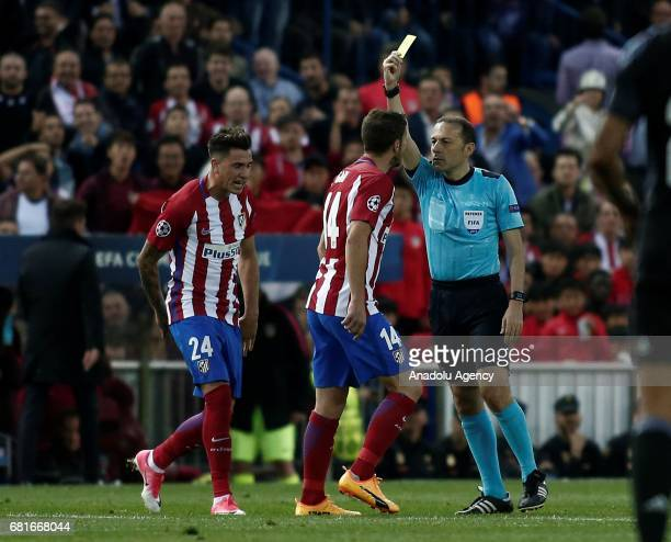 Referee Cuneyt Cakir shows a yellow card to Gabi of Atletico Madrid during the UEFA Champions League semi final second leg match between Atletico...