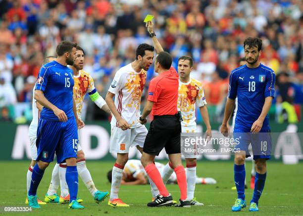 Referee Cuneyt Cakir shows a yellow card to Spain's Sergio Busquets