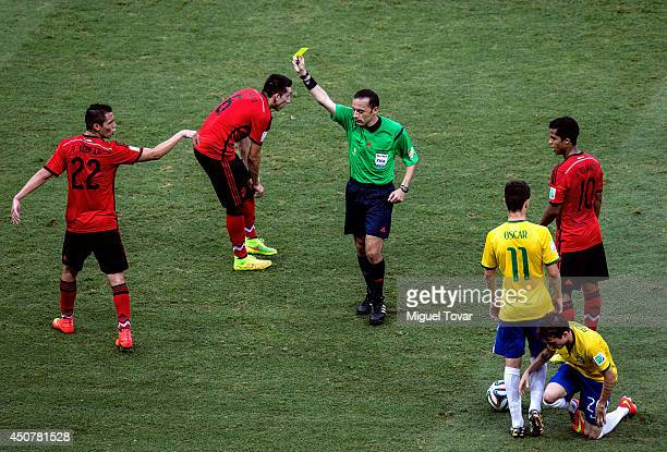 Referee Cuneyt Cakir shows Paul Aguilar of Mexico a yellow card during the 2014 FIFA World Cup Brazil Group A match between Brazil and Mexico at...