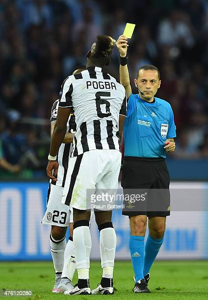 Referee Cuneyt Cakir shows the yellow card to Paul Pogba of Juventus during the UEFA Champions League Final between Juventus and FC Barcelona at...