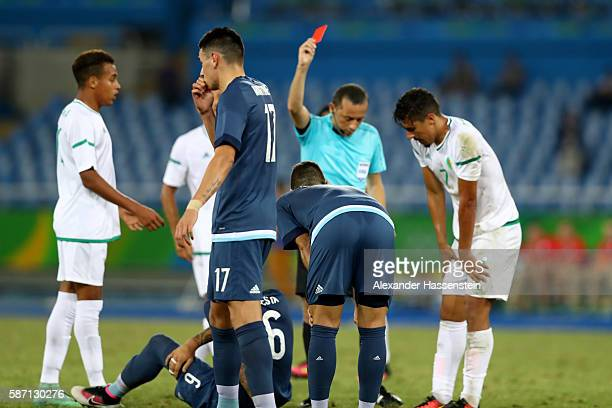 Referee Cuneyt Cakir shows Victor Cuesta of Argentina the red card during the Men's Group D first round match between Argentina and Algeria during...