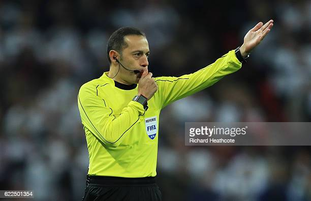 Referee Cuneyt Cakir signals during the FIFA 2018 World Cup qualifying match between England and Scotland at Wembley Stadium on November 11 2016 in...