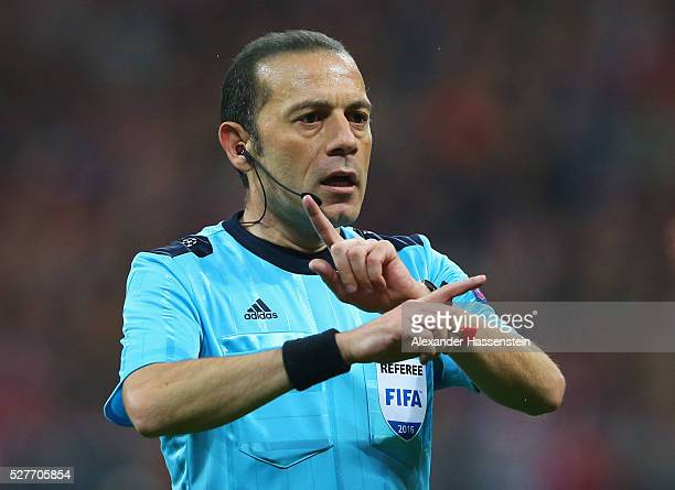 Referee Cuneyt Cakir signals during UEFA Champions League semi final second leg match between FC Bayern Muenchen and Club Atletico de Madrid at...