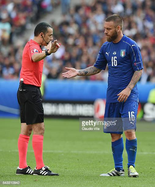 Referee Cuneyt Cakir talks to Daniele De Rossi of Italy during the UEFA EURO 2016 round of 16 match between Italy and Spain at Stade de France on...
