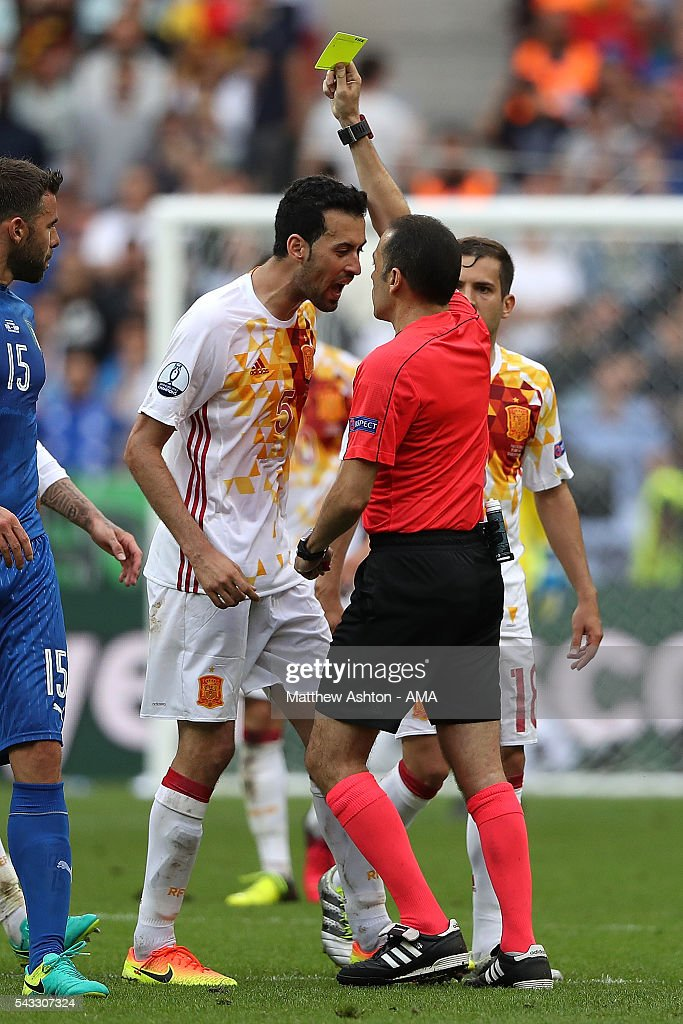Referee Cunyet Cakir books <a gi-track='captionPersonalityLinkClicked' href=/galleries/search?phrase=Sergio+Busquets&family=editorial&specificpeople=5477015 ng-click='$event.stopPropagation()'>Sergio Busquets</a> of Spain during the UEFA Euro 2016 Round of 16 match between Italy and Spain at Stade de France on June 27, 2016 in Paris, France.
