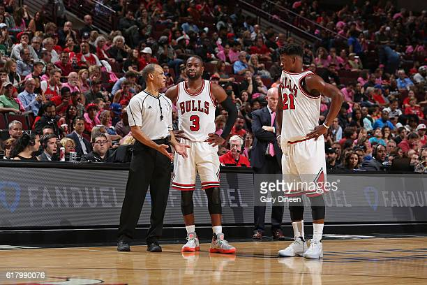 Referee Dan Crawford talks to Dwyane Wade and Jimmy Butler of the Chicago Bulls during an NBA preseason game against the Charlotte Hornets on October...