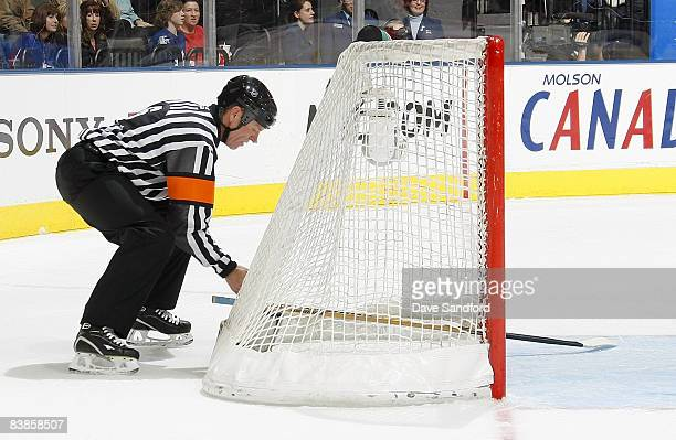 Referee Dan Marouelli tries to remove a stick from the net as the Toronto Maple Leafs face the Philadelphia Flyers during their NHL game at the Air...