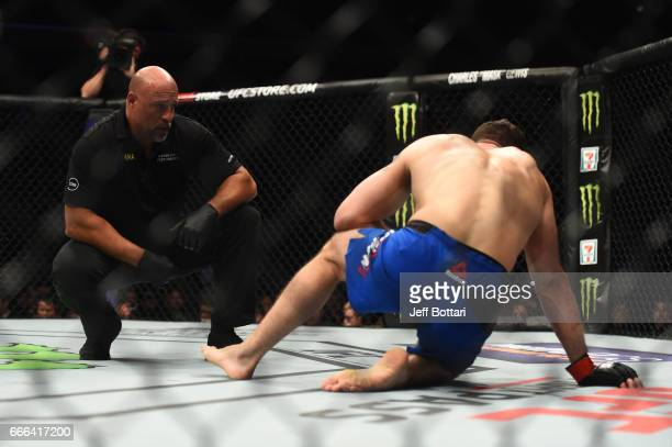Referee Dan Miragliotta talks with Chris Weidman during the UFC 210 event at the KeyBank Center on April 8 2017 in Buffalo New York