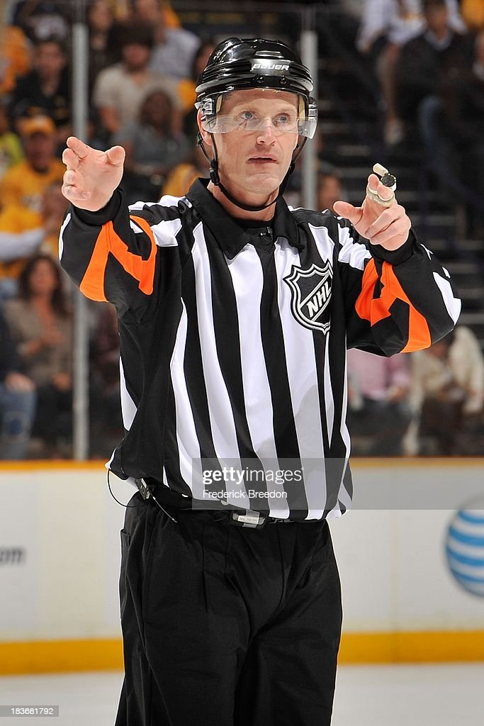Referee <a gi-track='captionPersonalityLinkClicked' href=/galleries/search?phrase=Dan+O%27Rourke&family=editorial&specificpeople=844097 ng-click='$event.stopPropagation()'>Dan O'Rourke</a> officiates a game between the Nashville Predators and the Minnesota Wild at Bridgestone Arena on October 8, 2013 in Nashville, Tennessee.