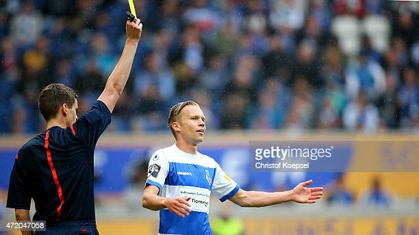 Referee Daniel Siebert shows Dennis Grote of Duisburg the yellow card during the Third League match between MSV Duisbrug and Preussen Muenster at...