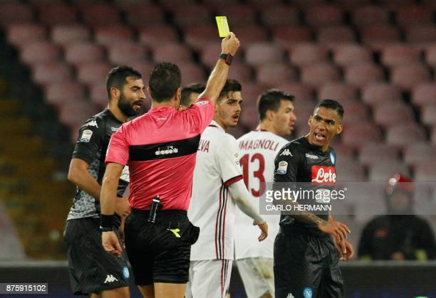 Referee Daniele Doveri gives a yellow card to Napoli's Brazilian midfielder Allan during the Italian Serie A football match SSC Napoli vs AC Milan on...