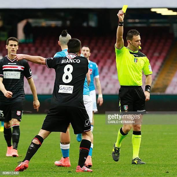 Referee Daniele Doveri shows a yellow card to Carpi's Italian midfielder Raffaele Bianco during the Italian Serie A football match SSC Napoli vs...
