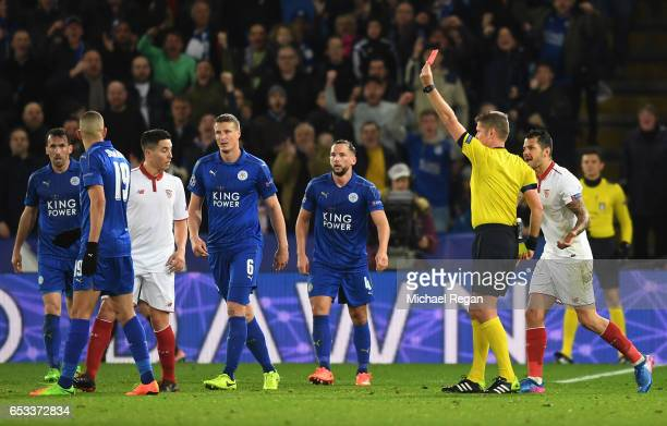 Referee Daniele Orsato of Italy shows the red card to Samir Nasri of Sevilla during the UEFA Champions League Round of 16 second leg match between...