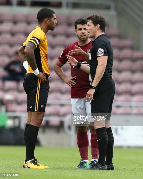 Referee Darren England makes a point to Joss Labadie of Newport County as Yaser Kasim of Northampton Town looks on during the PreSeason Friendly...