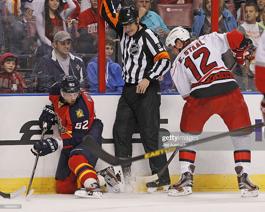 Referee Dave Jackson #8 calls a delayed penalty as Eric Staal #12 of the Carolina Hurricanes tries to dig the puck away from Tomas Kopecky #82 of the Florida Panthers during the season opener at the BB&T Center on January 19, 2013 in Sunrise, Florida. The Panthers defeated the Hurricanes 5-1.
