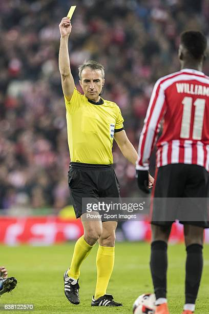 Referee David Fernandez Borbalan shows the yellow card to Raul Garcia of Athletic Club as Andres Iniesta Lujan of FC Barcelona lies on the pitch...