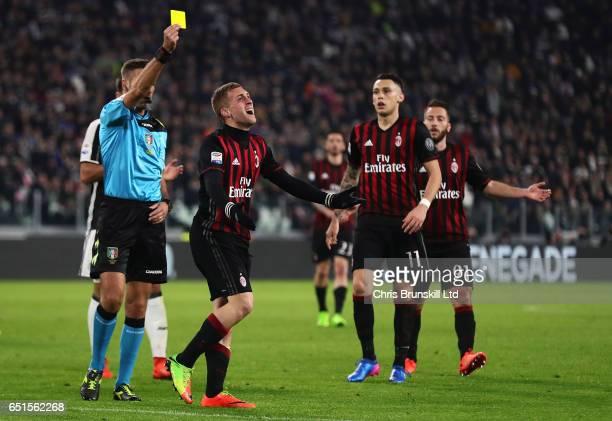 Referee Davide Massa shows Gerard Deulofeu of AC Milan a yellow card during the Serie A match between Juventus FC and AC Milan at Juventus Stadium on...