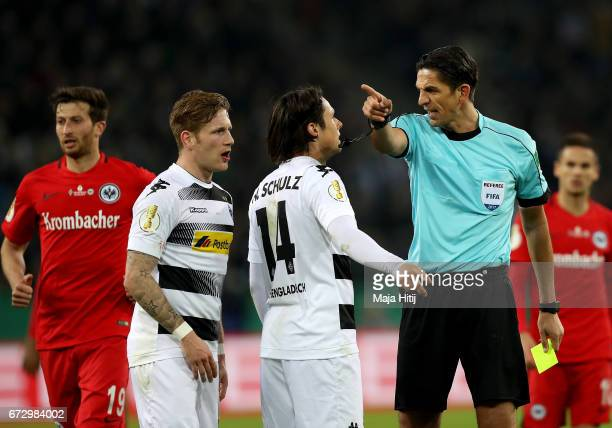 Referee Deniz Aytekin argues with Nico Schulz of Moenchengladbach during the DFB Cup semi final match between Borussia Moenchengladbach and Eintracht...