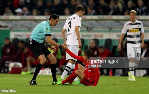 Referee Deniz Aytekin gives a helping hand to Mijat Gacinovic of Frankfurt during the DFB Cup semi final match between Borussia Moenchengladbach and...