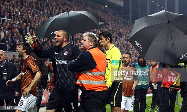 Referee Deniz Aytekin is protected by umbrellas after the Bundesliga match between FC St Pauli and FC Schalke 04 at Millerntor Stadium on April 01...