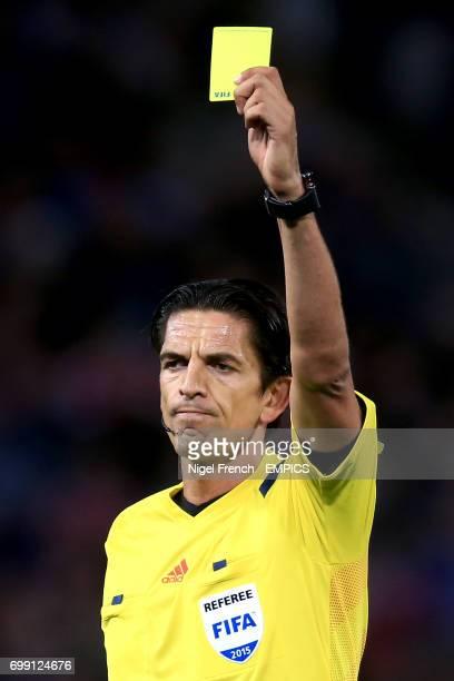 Referee Deniz Aytekin issues a yellow card