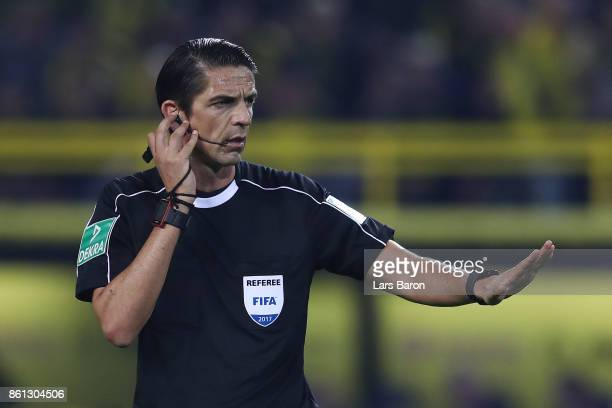 Referee Deniz Aytekin listens to the video referee to clarify a situation that eventually leads to a penalty for Dortmund during the Bundesliga match...